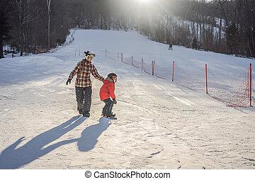 Mother teaches son snowboarding. Activities for children in winter. Children's winter sport. Lifestyle