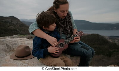 Mother teaches son to play guitar sitting together on the coast on a stone.