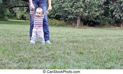 Mother teaches the eight-months daughter to go
