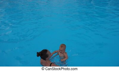 Mother teaches to swim an one-year-old kid in pool