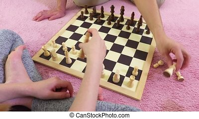 Mother teaching chess her daughter