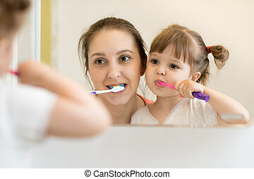 mother teaching child daughter teeth brushing