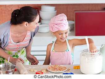 Young mother in kitchen teaching child how to cook