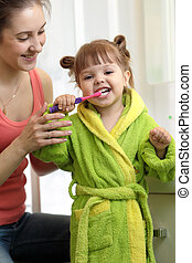 mother teaching daughter child teeth brushing in bathroom