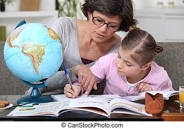 Mother teaching daughter geography