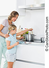 Mother teaching daughter how to cook at home