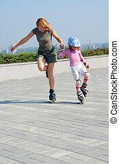 mother teaching daughter rollerblading