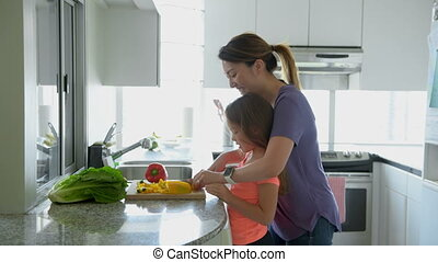 Mother teaching daughter to chop vegetables in kitchen 4k -...