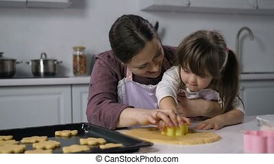 Mother teaching girl with down syndrome to bake - Caring...