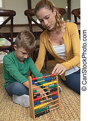 Mother teaching her son mathematics with abacus in a comfortable home