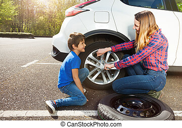 Mother teaching her son to change a wheel of car - Portrait ...