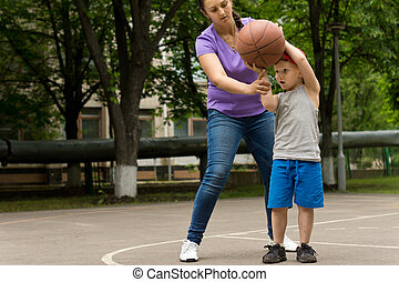 Mother teaching her son to play basketball