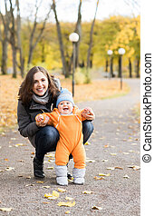 Mother teaching her toddler son to walk in the park