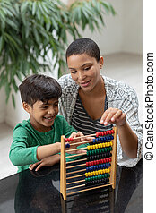 Mother teaching his son about abacus on a table