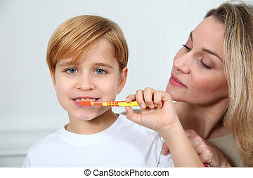 Mother teaching little boy to brush his teeth