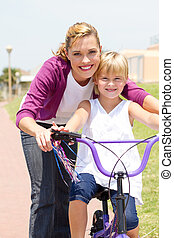 mother teaching little girl bicycle