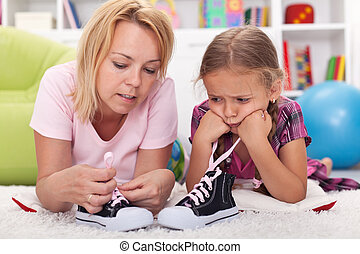 Mother teaching little girl to tie her shoes