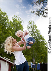 Mother Throwing Son in Air