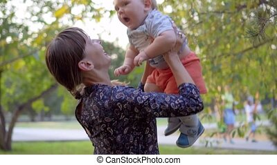 Mother throwing up her baby boy. They are laughing. Slow motion in the park.