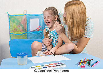 Mother tickles the cheek with a brush to paint his daughter, five-year