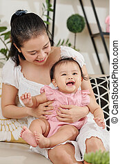 Mother tickling daughter - Smiling pretty young Asian woman ...