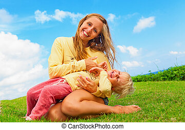 Mother tickling funny baby son lying on her laps - Happy ...