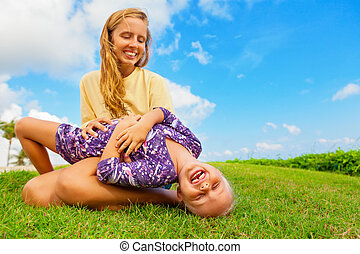 Mother tickling funny baby son lying on her laps