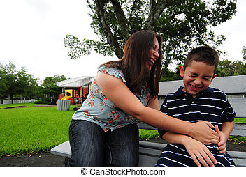 mother tickling son and laughing