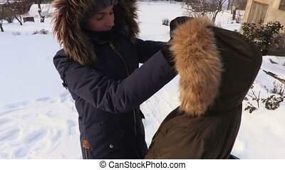Mother tidy up daughters winter coat