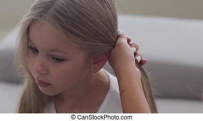 mom makes her little daughter hair, tying her hair in a ...