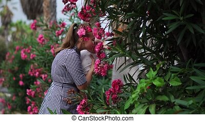 Mother to child plays a hugs and kisses baby around palm trees with flowers at the resort. Happy family