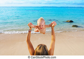 Mother tossing to mid air happy baby on sea beach
