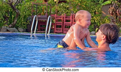 mother tossing up her toddler son in the water in outdoor swimming pool. Tropical resort on background.