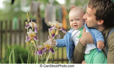 Mother touching baby with a flower after a rain. Handsome boy less than a year