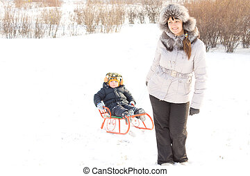 Mother towing her son in the snow