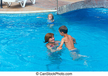 Mother train children to swim in the pool.