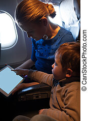 Mother traveling on a plane with her small son
