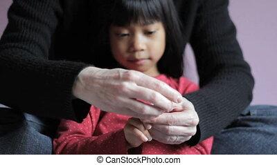 Mother Trims Daugters Fingernails - A cute little Asian 5...