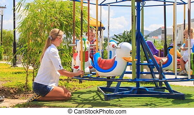 mother turns fast two girls with hairtails on merry-go-round