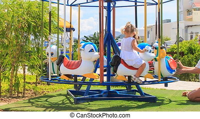 mother turns two little girls with hairtails on merry-go-round