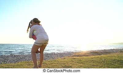 Mother twists daughter in her arms