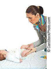 Mother undressing newborn baby
