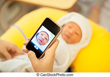 Mother use cellphone capture baby.