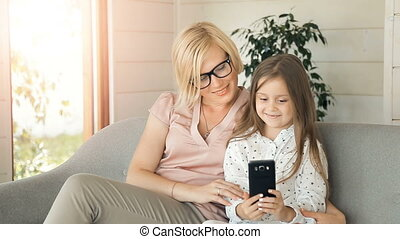 Mother Uses Phone with Daughter - Caring mother using phone...