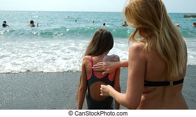 Mother uses sunscreen on her daughter on the beach. 4k. Slow...