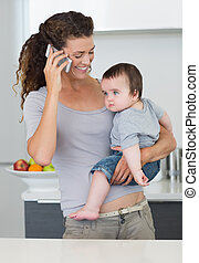 Mother using cellphone while carrying baby