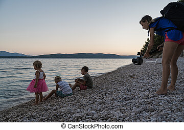Mother using gimbal holder as she take a video shot of her kids on the beach