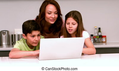 Mother using laptop with her childr