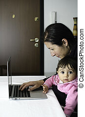 Mother using Laptop with her Daughter