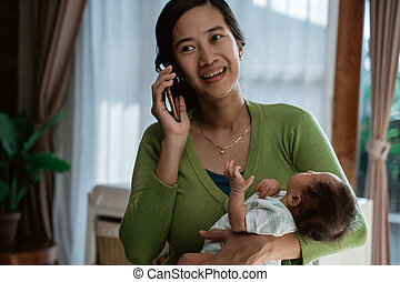 mother using mobilephone when holding little daughter